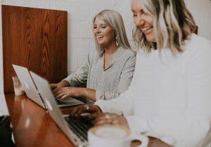 Laughing Businesswomen Working at Laptop